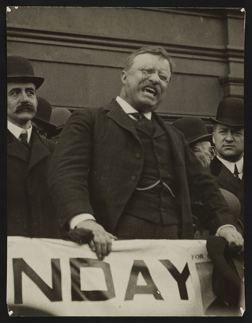 [Theodore Roosevelt speaking with intensity from platform]