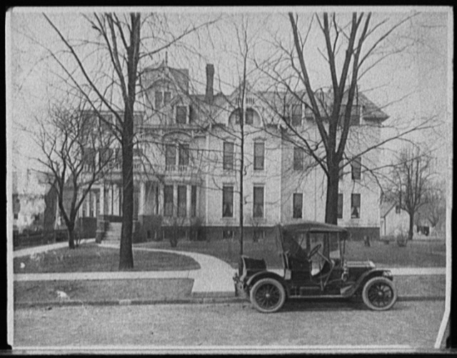 [Three-story house with side porch and automobile in front, possibly Detroit, Mich.]