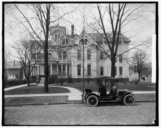 [Three-story house with side porch and automobile in front, possibly Detroit, Michigan]