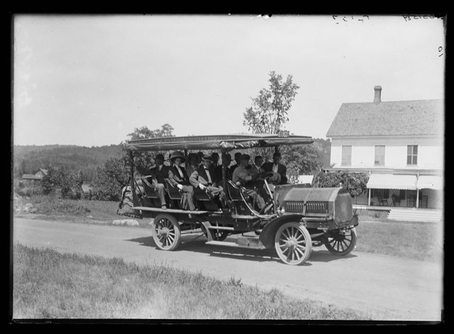 [Tour bus on road, probably in Adirondack mountains]