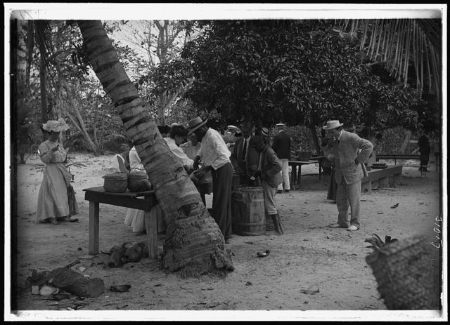 [Tourists buying coconuts and fruit from vendor, probably Nassau, Bahamas]