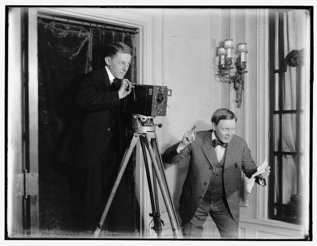 [Two men using a movie camera indoors]