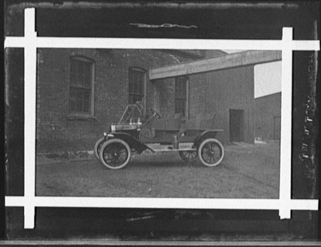 [Two-seater automobile in front of industrial building]