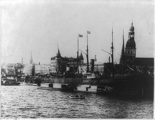 [View of Riga, Latvia with waterfront in foregrd; freighter ERIK and lumber barges]