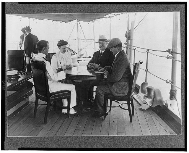 [William Howard Taft seated at table playing cards with his wife and two men on boat enroute to Philippines]