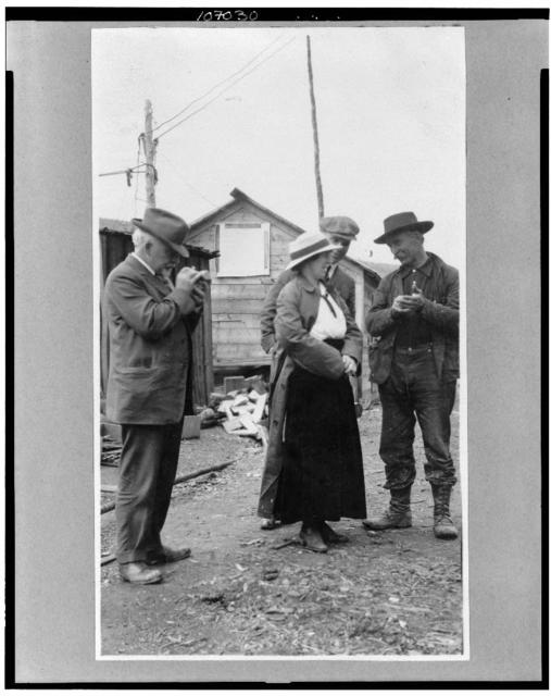 [Woman and three men talking outside]