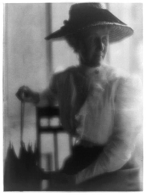 [Woman in straw hat and white blouse with umbrella, seated]