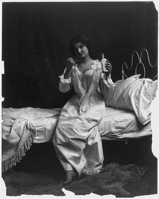 [Woman seated on bed and taking spoonful of medicine]