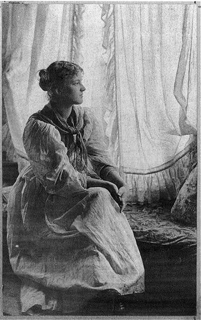 [Woman seated with crossed legs in front of sheer curtains] / Mary A. Bartlett.