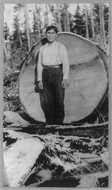 Wood cutter standing in front of log with a diameter almost equal his height