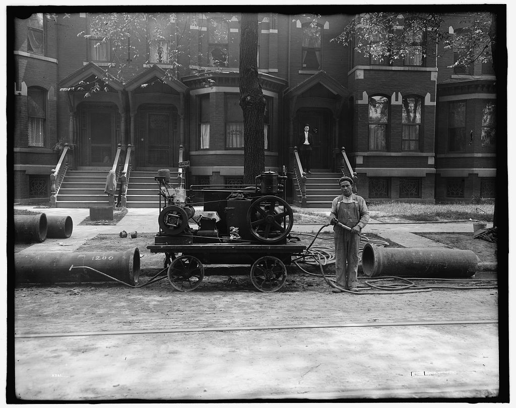 [Worker, possibly doing pipeline construction for gas company, with cables and engine]
