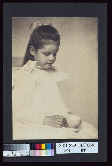 [Young girl in white dress, seated holding teacup and saucer] / A.P.