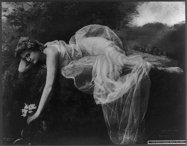 [Young woman in graceful gown, full lgth., lying on bank and touching flower in water]