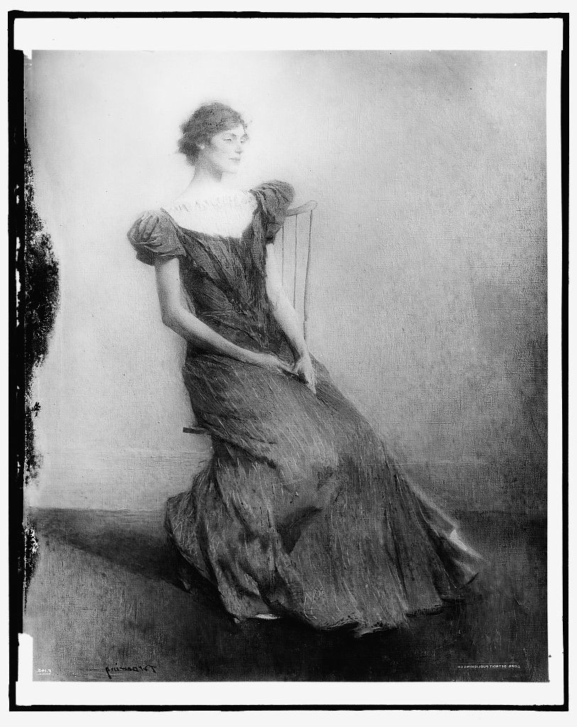 [Young woman seated in chair]