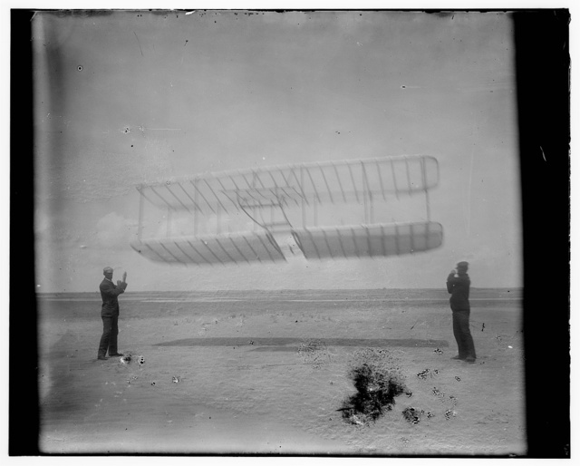 [1901 glider being flown as a kite, Wilbur at left side, Orville at right; Kitty Hawk, North Carolina]