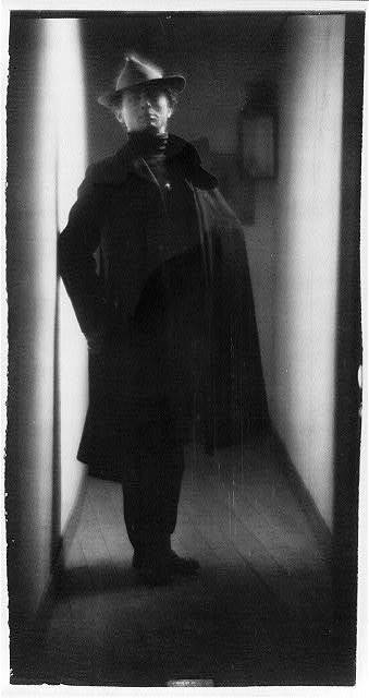 [Edward Steichen, in coat and hat, standing in hallway, portrait]