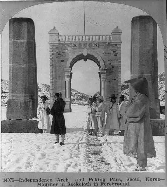 Independence arch and Peking Pass, Seoul, Korea - mourner in sackcloth in foreground