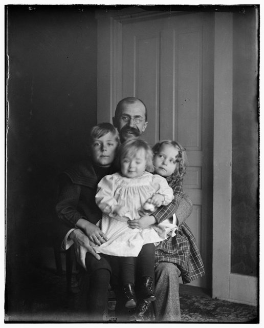 [Lorin Wright, brother of Wilbur and Orville, seated holding his children, Horace, Ivonette, and Leontine]