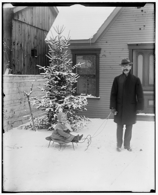 [Lorin Wright pulling his daughter Leontine, age three, on a sled]