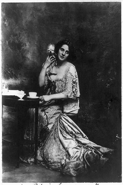 [Mrs. Patrick Campbell, actress, full-length portrait, seated at small table, facing slightly right, holding pet dog]