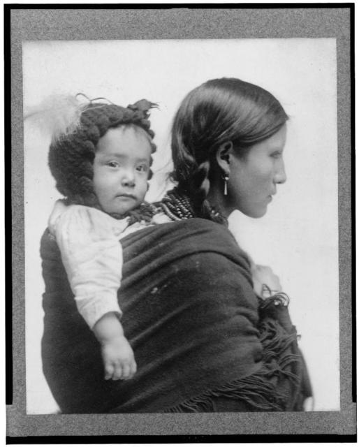 [Native American woman from Plains region, half-length portrait, facing right, with baby on her back] / Beach, N.Y.