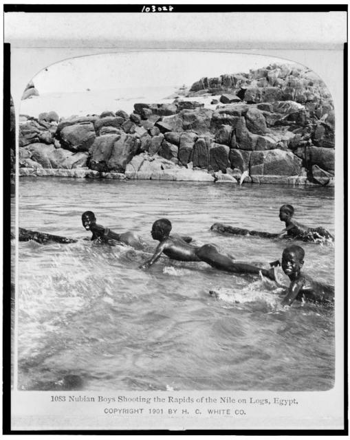 Nubian boys shooting the rapids of the Nile on logs, Egypt
