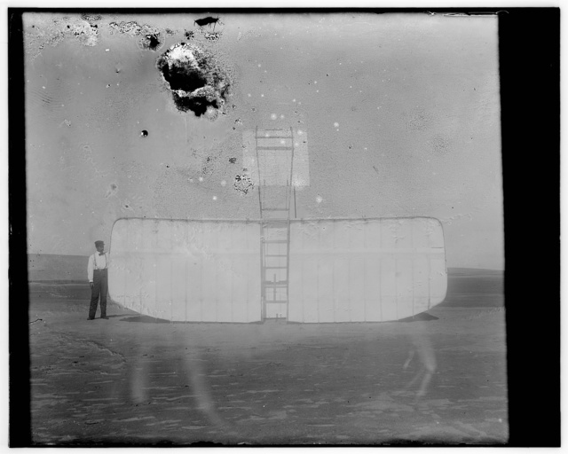 [Orville at left wing end of upended glider, bottom view; Kitty Hawk, North Carolina]