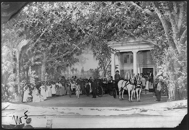 "[Scene from stage production of ""Uncle Tom's Cabin"", 1901]: crowd scene in front of plantation house; Uncle Tom standing between girl in pony cart and couple in carriage"