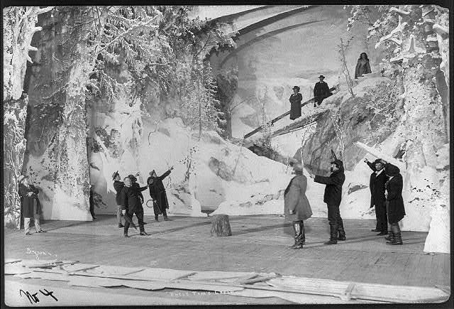 "[Scene from stage production of ""Uncle Tom's Cabin"", 1901]: group of men, two holding whips, pointing at two men and a woman on snow-covered bridge"