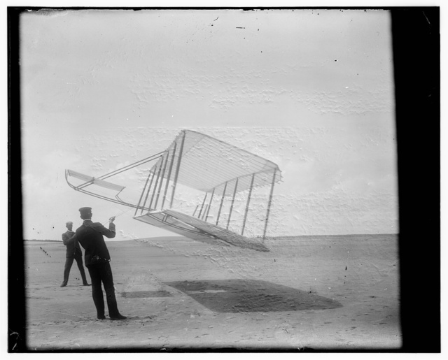 [Side view of glider flying as a kite near the ground, Wilbur at left and Orville at right, glider turned forward to right and tipped downward]