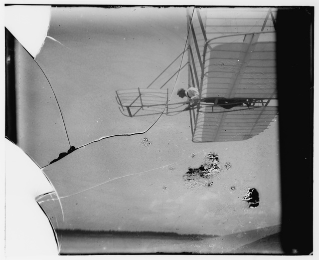 [Side view of Wilbur Wright piloting a glider in level flight almost overhead, moving to left, showing bottom wing and elevator]