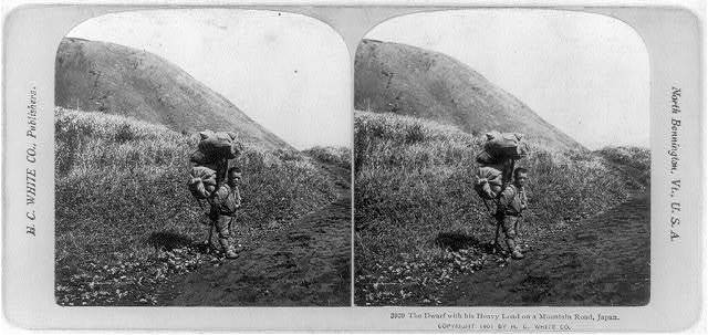 The dwarf with his heavy load on a mountain road, Japan