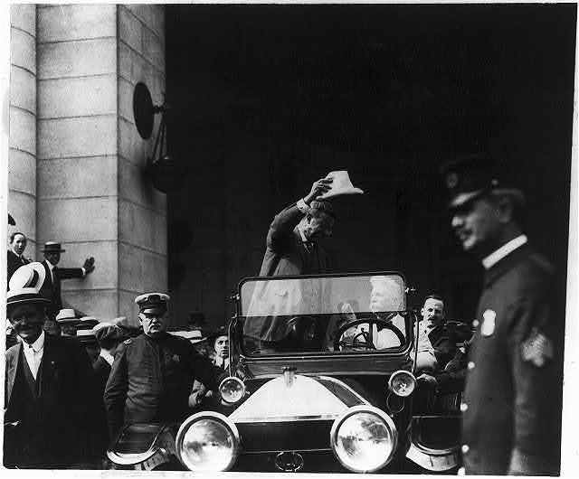 [Theodore Roosevelt, standing in open automobile, waving his hat]