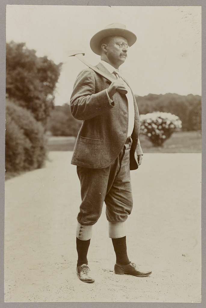 [Theodore Roosevelt wearing knickerbockers and carrying an axe on his shoulder]