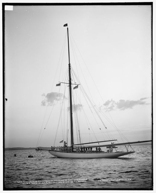 Victorious Columbia at mooring in the horseshoe after race of Oct. 4, 1901, flying winning pennants