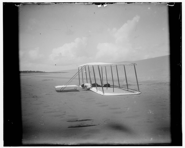 [Wilbur Wright in prone position on glider just after landing, its skid marks visible behind it and, in the foreground, skid marks from a previous landing; Kitty Hawk, North Carolina]