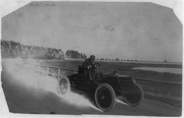 [Winton driving his automobile on racetrack]
