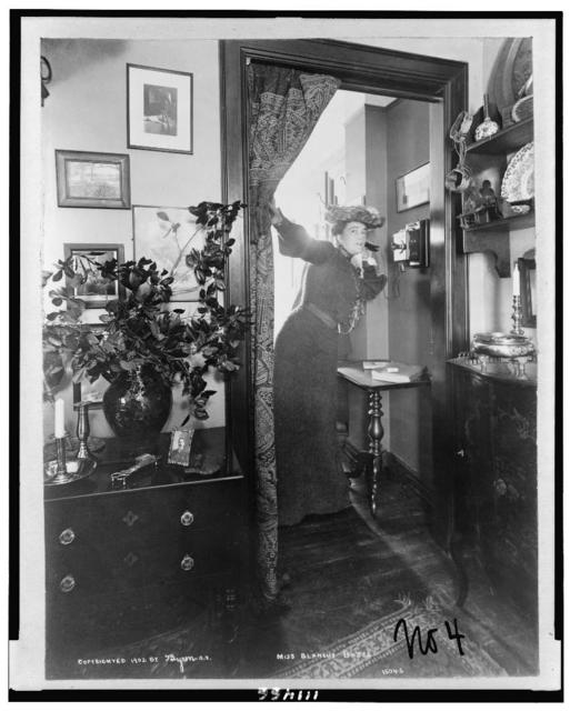 [Blanche Bates, full-length portrait, standing, facing right, on telephone]