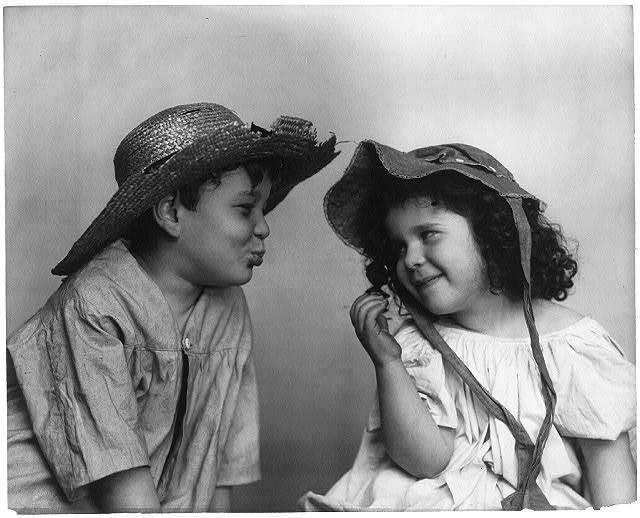 [Boy wearing broken straw hat, with lips puckered, facing girl wearing bonnet]