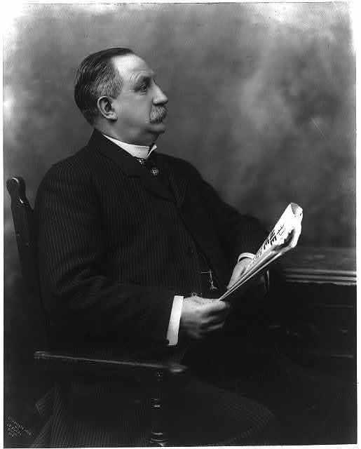[E.P. Shaw, three-quarters length, seated, holding newspaper]