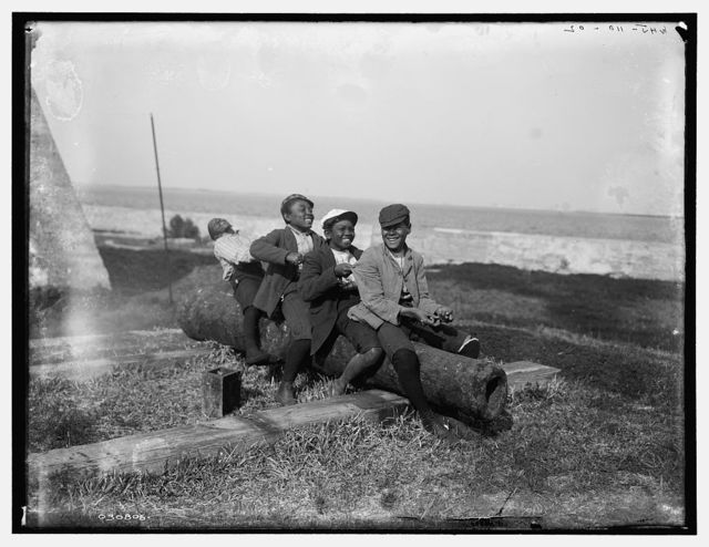 [Four black boys sitting on a cannon by a waterfront]