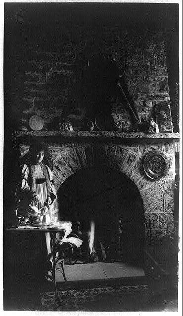 [Helena Modjeska, full-length portrait, standing, facing right, pouring from tea kettle in front of fireplace]