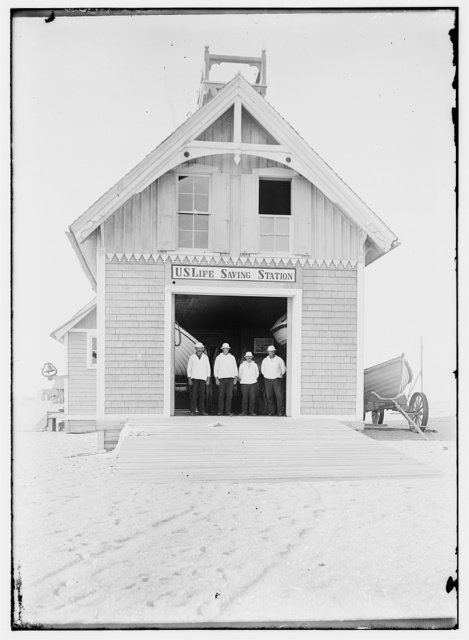 [Kill Devil Hills Lifesaving Station, with four crew members wearing white hats and jackets standing in doorway, and a boat near outer wall at right; Kitty Hawk, North Carolina]