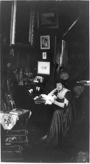 [Mme. Helena Modjeska, full-length portrait, seated at desk, facing left, surrounded by pictures]