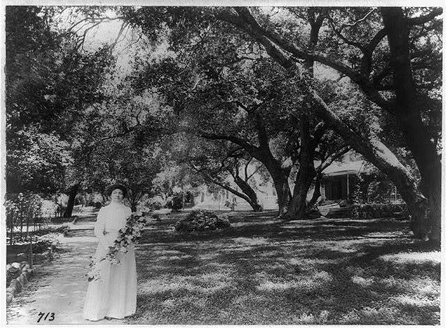 [Mme. Helena Modjeska, full-length portrait, standing, facing front, holding flowers outside her home, California]