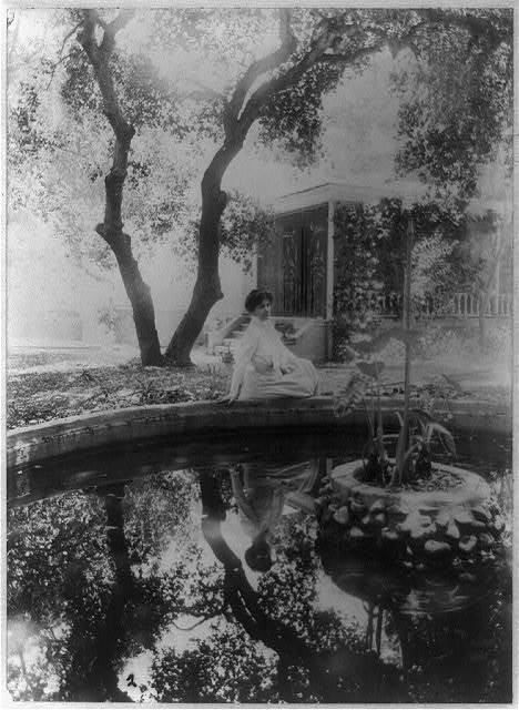 [Mme. Helena Modjeska, three-quarter length portrait, seated, facing slightly right, beside pond outside her house, California]