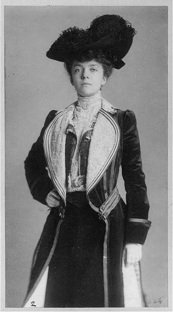 [Mrs. Alice Roosevelt Longworth, three-quarter length portrait, standing with right hand on hip, wearing coat and hat]
