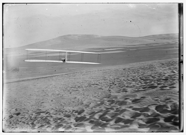[Orville making right turn, showing warping of wings, hill visible in front of him; Kitty Hawk, North Carolina]