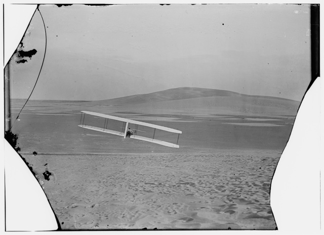 [Rear view of Wilbur making a right turn in glide from No. 2 Hill, right wing tipped close to the ground]