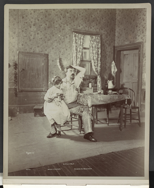 "[Scene from ""Little Italy"" showing child actress Helen Stevenson sitting on the lap of Frederic de Belleville]"